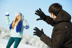 Young peolple playing snowballs in winter. Happy young people playing snowballs in sunny winter outdoors Royalty Free Stock Image