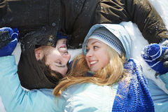 Young peolple on snow in winter. Happy young people laying on snow in winter outdoors Stock Photography