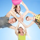 Young people across blue sky Royalty Free Stock Image