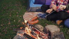 Young people bake sausages on fire. Picnic in the woods stock video footage