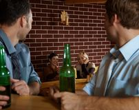 Young people in bar. Young people sitting in bar, young men looking at smiling women sitting at table Royalty Free Stock Image