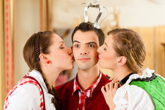 Young people in Bavarian Tracht in restaurant Stock Photos