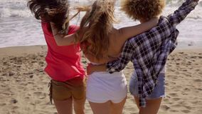 Young People On The Beach. Three young girlfriends barefoot go towards the water at the beach while hop around cheerfully in slow motion stock video