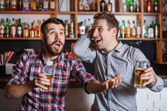 Young people with beer watching football in a bar Stock Photos