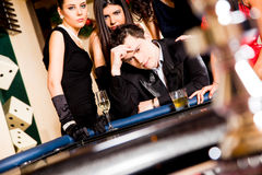 Young people behind roulette table Royalty Free Stock Photos