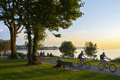 Young people biking and walking at Stanley Park late afternoon royalty free stock images