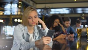 Young people bored in bar, using phones instead of live communication, addiction. Stock footage stock footage