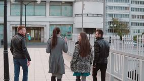 Young people on a bridge. Two pretty girls and two handsome young men talk on the go. Slow mo, back view, steadicam shot. Back view of beautiful young people stock video