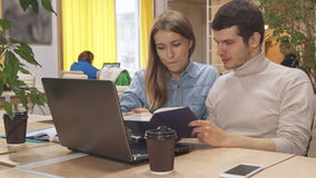 Young people browse some book at the working hub stock video footage