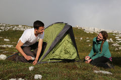 Young people building up a tent in the mountains Royalty Free Stock Photo