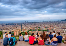Young people on Bunkers del Carmel, Barcelona, Spain. Young people gathered on Bunkers del Carmel over Barcelona skyline with blue skies in Spain stock photos