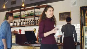 Young people are buying coffee-to-go in nice local cafe and paying with smartphone while friendly workers are greeting