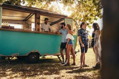 Group of young people at food truck. Young people buying street food from a food truck at park. Group of men and women at food truck royalty free stock photography