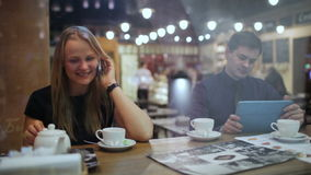 Young people in a cafe with phone and Tablet PC. Young woman in a cafe talking on the phone sitting next to the man using touchpad stock video footage