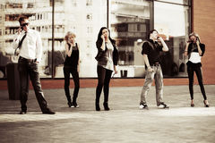 Young fashion people calling on the cell phones on a street  Royalty Free Stock Photos