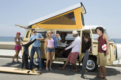 Young People By Campervan. Multiethnic group of young people by campervan royalty free stock photo