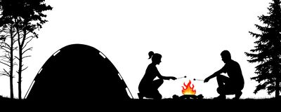 Young people camping in nature near the tent. Man and woman are frying marshmallows at the stake. Trekking in the forest.