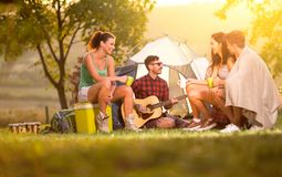 Young people on camping trip spending time together. Young people on camping trip spending time together with music guitar and song over sunset stock image