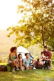 Young people on camping trip to play and sing royalty free stock photography