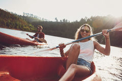 Young people canoeing in a lake Stock Photography