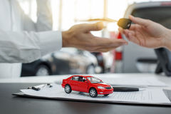 Young People in a Car Rental Service Transportation Concept. Young men and women in a car rental service lease contract Royalty Free Stock Photography