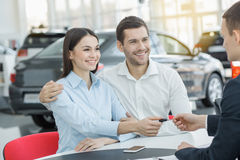 Young People in a Car Rental Service Transportation Concept. Young men and women in a car rental service lease contract royalty free stock images