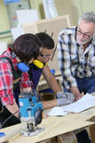 Young people in carpentry training with professor. Young people in carpentry course with teacher Royalty Free Stock Image