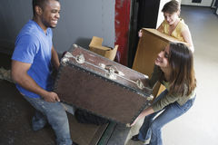 Young people carrying heavy box on moving day. Royalty Free Stock Image