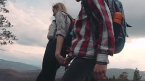 Young people in casual wear with backpacks wandering on the top of the hills, chatting, holding their hands, laughing. Love story. Extreme adventure, gorgeous stock video footage