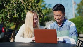 Young people caucasian woman and Chinese man are using laptop together. Have a rest on a outdoors cafe stock video