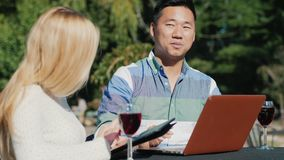 Man and woman relaxing in a cafe, drinking wine. Use laptop and tablet. Young people caucasian woman and Chinese man are using laptop together. Have a rest on a stock footage