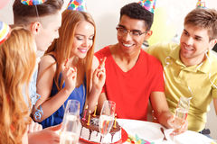 Young people celebrating a birthday sitting at the Royalty Free Stock Photography