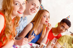Young people celebrating a birthday sitting at the Royalty Free Stock Images