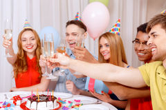 Young people celebrating a birthday sitting at the Stock Photo