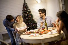 Young people celebrating Christmas and opening presents in the r royalty free stock photography