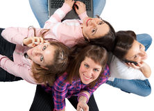 Young people with cellphones and laptop. Group of young people and teens shot from above, isolated on white, with cellphones and laptop, smiling, having fun Royalty Free Stock Photography