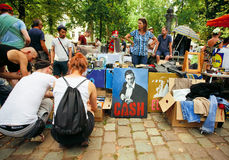 Young people choosing books, draws, portrait of Johnny Cash on street market Royalty Free Stock Photos