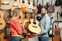Young people choosing guitar in store stock images