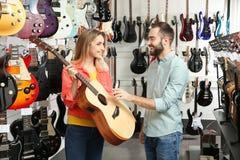 People choosing guitar in music store stock photos