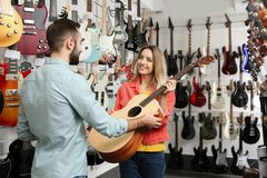 Young people choosing guitar in store stock image
