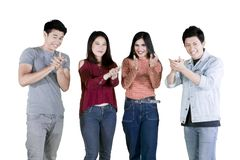 Young people clap their hands together on studio. Group of young people clapping their hands together and smiling at the camera in the studio stock photo