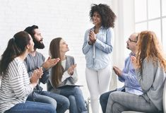 Young people clapping to woman at rehab group meeting royalty free stock photo