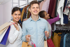 Young people in a clothing store. Happy young people in a clothing store with shopping bags in their hands Royalty Free Stock Images
