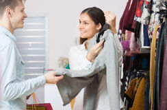 Young people in a clothing store. The seller in a clothing store offers goods to the young man royalty free stock photo
