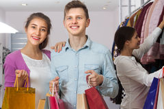 Young people in a clothing store. With shopping bags in their hands royalty free stock photography