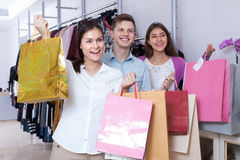 Young people in a clothing store. Smiling young people in a clothing store with shopping bags Royalty Free Stock Image