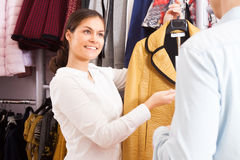 Young people in a clothing store. Young women offering a coat in a clothing store royalty free stock photo