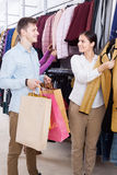 Young people in a clothing store. Young women offering a coat in boutique royalty free stock photos