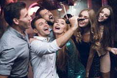 Young people in the club dance and sing. A man in a white shirt is holding a microphone and singing. Young people in the club dance and sing. A men in a white stock photos