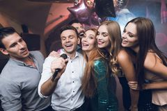 Young people in the club dance and sing. A man in a white shirt is holding a microphone and singing. Royalty Free Stock Images